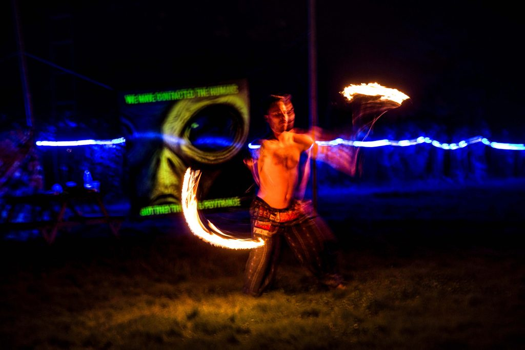 Dancer with fire torches. In the backround is a banner with an Alien,that says: We have contacted the humans but they think is psytrance.
