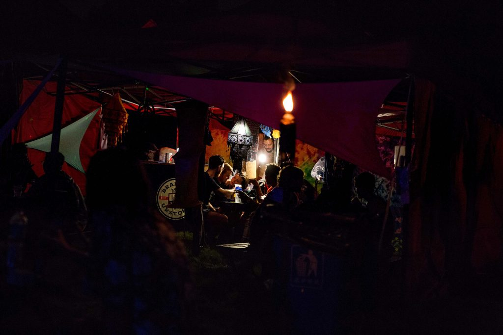 young hippies chilling in tents. With candles and lanterns.