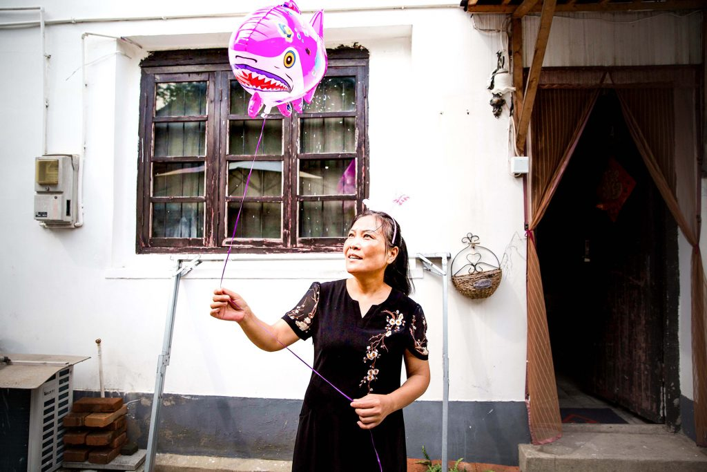 Smiling Chinese woman in Zhujiajiao holding a pink helium balloon that looks like a pink shark. Shalanaya Psytrance Festival in China.
